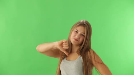 Charming-Girl-Expressing-Disapproval-Standing-On-Green-Background-And-Showing