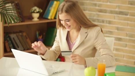 Encantadora-Niña-Sentada-En-La-Mesa-Usando-Laptop-Con-Tarjeta-De-Crédito-Mirando