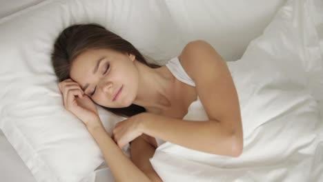 Charmantes-Mädchen-Das-Im-Bett-Schläft-Aufwacht-Und-Lächelt