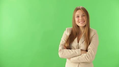 Encantadora-Mujer-Joven-Posando-Sobre-Fondo-Verde-Con-Los-Brazos-Cruzados