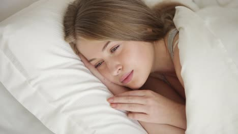 Charming-Young-Woman-Sleeping-In-Bed-Opening-Her-Eyes-Looking-At-Camera