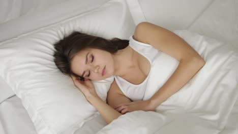 Charming-young-woman-sleeping-in-bed-waking-up-looking-at-camera-and-smiling