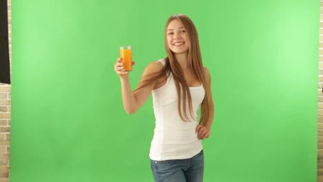 Cheerful-girl-standing-on-green-background-holding-glass-of-juice-looking-at-camera-and-smiling