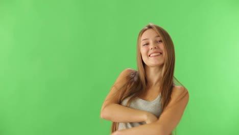 Alegre-Niña-De-Pie-Sobre-Fondo-Verde-Mostrando-Con-La-Mano-A-La-Izquierda-Y-Sonriendo