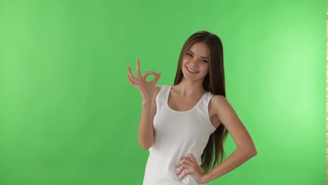 Cheerful-Girl-Standing-On-Green-Background-Smiling-At-Camera-And-Showing-Ok