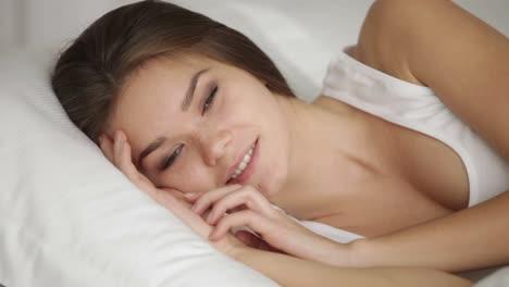 Fröhliche-Junge-Frau-Die-Im-Bett-Liegt-Und-In-Die-Kamera-Schaut-Und-Lächelt