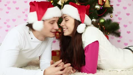 Couples-In-Love-In-Santa-Hats-Lying-On-The-Floor-And-Kiss