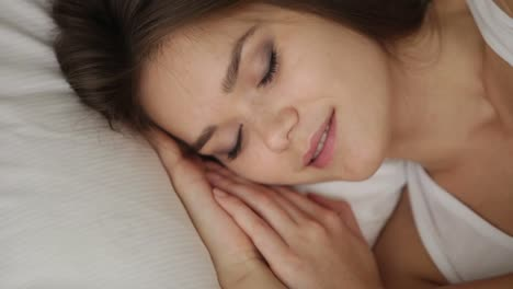Süßes-Mädchen-Das-Im-Bett-Schläft-Und-Ihre-Augen-öffnet-In-Die-Kamera-Schaut-Und-Lächelt