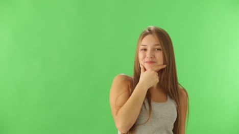 Cute-Girl-Standing-On-Green-Background-Expressing-Surprise-Pointing-Her-Finger