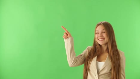 Cute-Young-Woman-On-Green-Background-Smiling-And-Pointing-Her-Finger