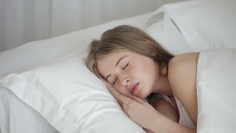 Linda-Mujer-Joven-Durmiendo-En-La-Cama-Moviéndose-Y-Sonriendo-En-Su-Cámara-Panorámica-De-Sueño