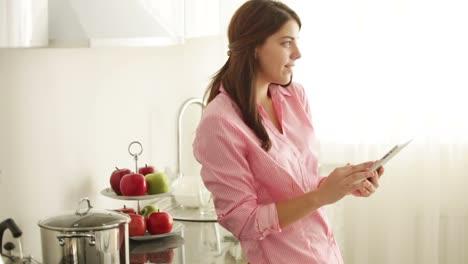 Linda-Mujer-Joven-De-Pie-En-La-Cocina-Con-Touchpad-Y-Sonriente-Cámara-Panorámica