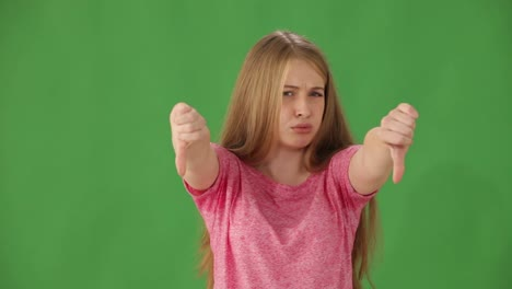 Frowning-Young-Woman-Standing-On-Green-Background-Shaking-Her-Head-No