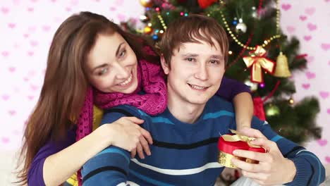 Girl-Gives-Her-Boyfriend-A-Gift-Near-Christmas-Tree