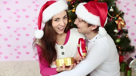 Girl-Opens-The-Gift-And-The-Laughter-Couple-In-Love-Sitting-Near-A-Christmas