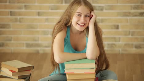 Happy-Girl-Sitting-On-Floor-With-Books-Looking-At-Camera-And-Smiling-Panning
