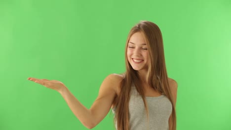Happy-young-woman-standing-on-green-background-looking-at-camera-and-smiling