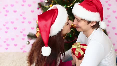 Love-Couple-In-Santa-Hats-Near-Christmas-Tree