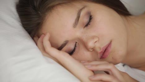 Hübsches-Mädchen-Das-Im-Bett-Schläft-Und-Ihre-Augen-öffnet-In-Die-Kamera-Schaut-Und-Lächelt