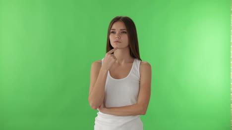 Linda-Chica-De-Pie-Sobre-Fondo-Verde-Apuntando-Su-Dedo-Hacia-Arriba-Mientras-Piensa