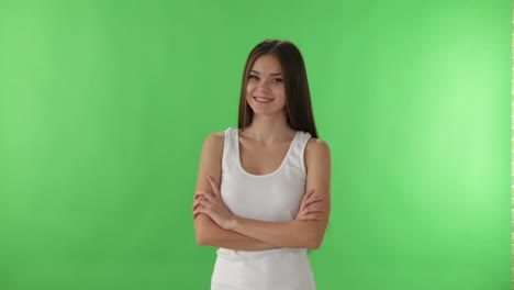 Linda-Chica-De-Pie-Sobre-Fondo-De-Pantalla-Verde-Sonriendo-Y-Mostrando-El-Pulgar-Hacia-Arriba-A-La-Cámara