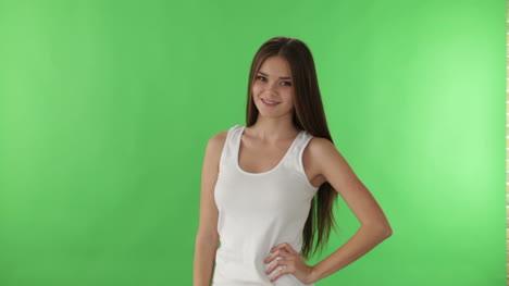 Chica-Guapa-De-Pie-Sobre-Fondo-Verde-Sonriendo-A-La-Cámara-Y-Mostrando-El-Signo-De-Ok