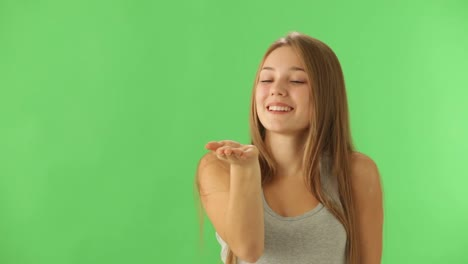 Pretty-Young-Woman-Posing-On-Green-Background-Blowing-Kiss-At-Camera-And-Smiling