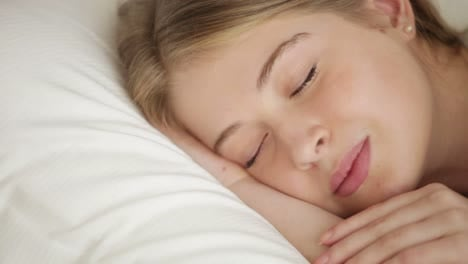 Pretty-Young-Woman-Sleeping-In-Bed-Opening-Her-Eyes-Looking-At-Camera-Closing