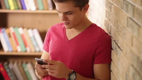 Young-man-leaning-against-wall-using-mobile-phone-looking-at-camera