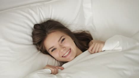 Young-Woman-Lying-In-Bed-Pulling-Up-Blanket-And-Smiling-At-Camera