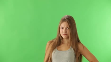 Young-Woman-Standing-On-Green-Background-Expressing-Discontent-And-Showing