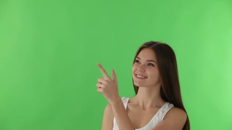 Young-Woman-Standing-On-Green-Background-Pointing-Her-Finger-Up-While-Thinking