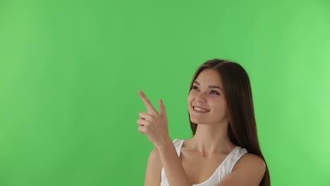 Mujer-Joven-De-Pie-Sobre-Fondo-Verde-Apuntando-Su-Dedo-Hacia-Arriba-Mientras-Piensa