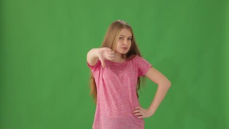Mujer-Joven-De-Pie-Sobre-Fondo-Verde-Mostrando-El-Pulgar-Hacia-Abajo