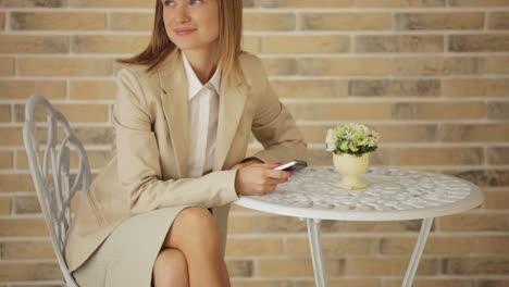 Attractive-Businesswoman-Sitting-At-Cafe-And-Holding-Cellphone