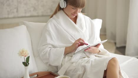 Attractive-Woman-In-Headset-Sitting-On-Bed-And-Using-Touchpad