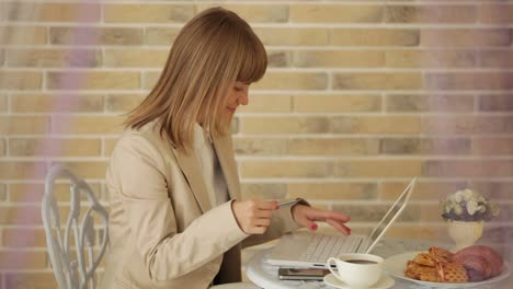 Attractive-Woman-Sitting-At-Cafe-With-Laptop-And-Credit-Card