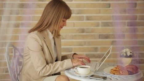 Atractiva-Mujer-Joven-Sentada-En-El-Café-Con-Laptop-Y-Taza-De-Café