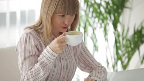 Atractiva-Mujer-Joven-Sentada-En-La-Mesa-Trabajando-En-La-Computadora-Portátil-Tomando-Café-Y