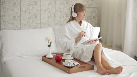 Beautiful-Woman-In-Headset-Sitting-On-Bed-And-Using-Touchpad