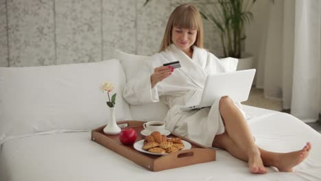Beautiful-Woman-Sitting-On-Bed-With-Laptop-And-Holding-Credit-Card