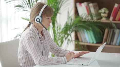 Hermosa-Mujer-Joven-En-Auriculares-Trabajando-En-Equipo-Portátil-Y-Sonriendo