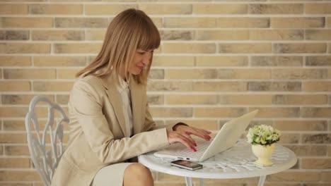 Hermosa-Mujer-Joven-Sentada-En-El-Café-Con-Computadora-Portátil-Y-Teléfono-Celular