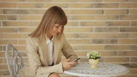 Businesswoman-Sitting-At-Cafe-And-Using-Mobile-Phone