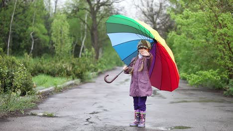 Cheerful-Little-Girl-Hiding-Behind-Umbrella-In-The-Park-Thumbs-Up-Waving-Hand