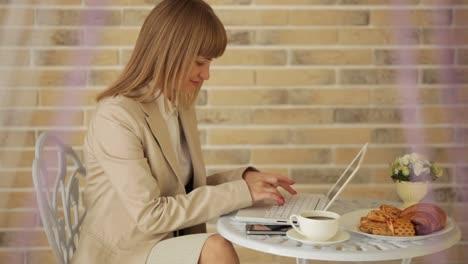 Alegre-Mujer-Joven-Sentada-En-El-Café-Con-Laptop-Y-Tarjeta-De-Crédito