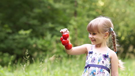 Child-Holding-A-Tomato-And-Looking-At-Camera