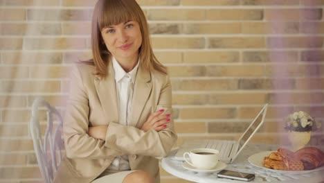 Linda-Mujer-Sentada-En-El-Café-Usando-Laptop-Y-Sonriendo-A-La-Cámara