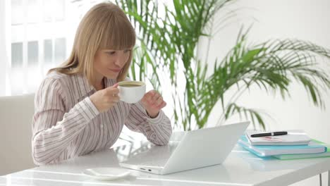 Cute-Young-Woman-At-Office-Working-On-Laptop-Drinking-Coffee-And-Smiling