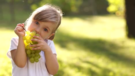 Girl-Eagerly-Eating-Grapes-Outdoors